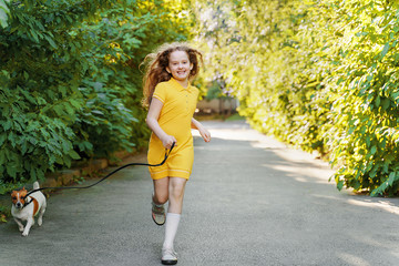 Cute girl run in a park with a puppy jack russell terrier. Happy friends leisure outdoors.