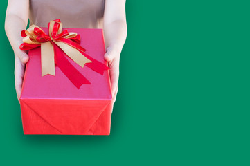 Woman hands holding christmas holiday gift red box on decorated festive on  isolated on green background,Packaging gift wrap,Concept of giving presents