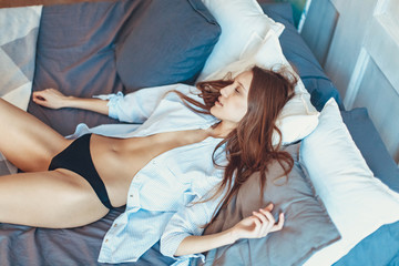 Perfect sexy woman with perfect skin, posing at bedroom, wearing sexy luxury stylish black lingerie In a shirt.l Lady lying on white bed