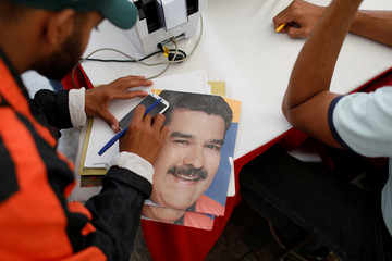 A leaflet with the image of the president of Venezuela, Nicolás Maduro, is seen during a transportation census in Caracas