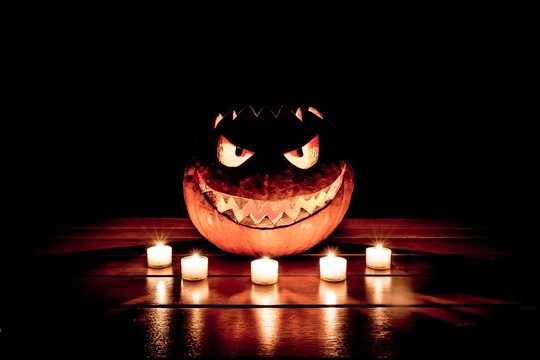Spooky smiling halloween pumpkin in burning fire candles flames. The big helloween symbol has a mad face glowing eyes mouth and glow teeth on wooden table. Black orange nightmare of October 31st