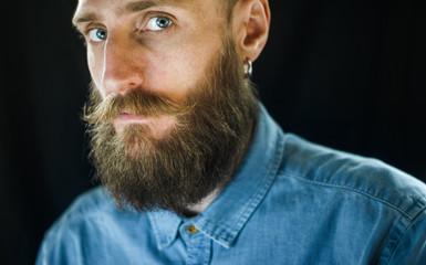Portrait of Bearded Man in a Blue Denim Shirt on Black Background. Piercing Glance Concept