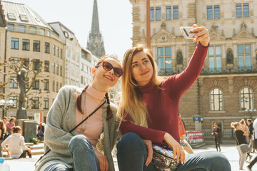 Two young woman taking selfie on smartfone