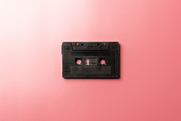 black tape cassette on pink background.