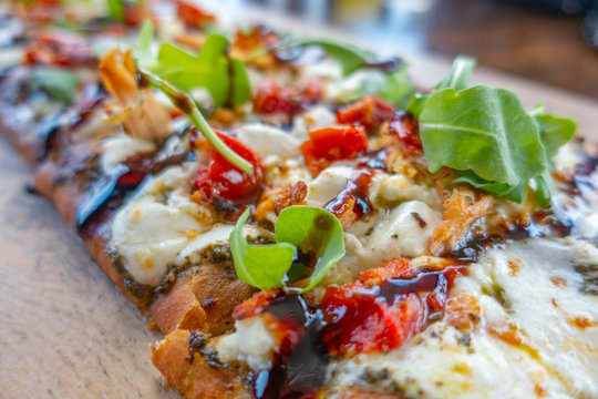 Chicken and Mozzarella Flatbread Pizza with herbs, tomatos and pesto sauce on wooden plate. Close up view .