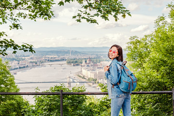 Happy asian casual woman student enjoying great view of the Parliament building in Budapest city, travel in Europe concept