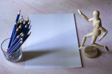 Colored pencils, empty paper and dummy for drawing on the table.