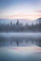 Trees reflect over the misty waters of Sparks Lake at sunrise in Central Oregon