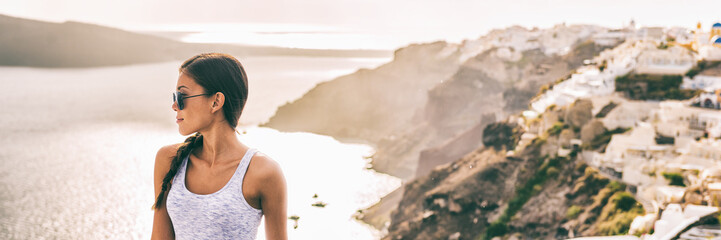 Wall Mural - Santorini travel Asian woman model posing against sunset flare in Oia village background landscape -banner panorama copy space.