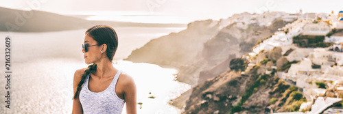 Wall mural Santorini travel Asian woman model posing against sunset flare in Oia village background landscape -banner panorama copy space.