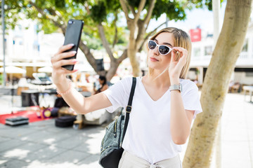 Young attractive playful tourist woman is making selfie on the phone outside, wearing sunglasses, light dress ourdoors