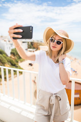 Young traveling woman holding phone making selfie against sea view. travel concept.