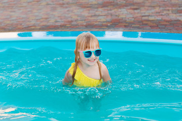 Little girl in a yellow swimsuit and sunglasses is swimming and jumping to swimming pool at resort. Summer fun in the pool.