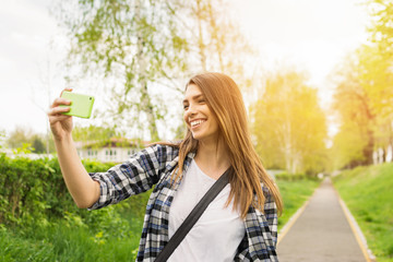 Young woman taking a selfie or filming a vlog video on smartphone outdoors in park. Beautiful blonde teenage girl filming or photographing herself outside on sunny day.