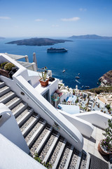 Gourgeous view of stairs in white walled town of Fira in Santorini, Greece, with ocean, cliffs and caldera of Santorini in the background.
