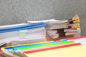 Close up pile of unfinished homework assignment and report stacked in archive with colorful plastic binding bars on teacher's desk waiting to be managed and checked. Education and business concept.