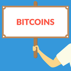 BITCOINS. Hand holding wooden sign