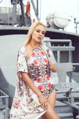 Beautiful and sexy fashion model posing in swimsuit in front of military vessel.