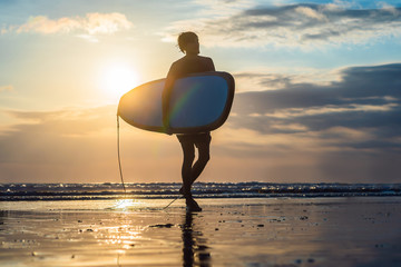 Vacation Silhouette Of A Surfer Carrying His Surf Board Home At Sunset With Copy Space