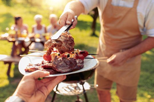 Family grilling meat on a barbecue