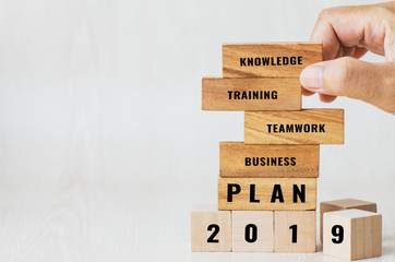 Ideas planning 2019 for Strategy plan risk in business concept : Businessman placing wooden blocks with letter e.g teamwork, knowledge, business, training etc. Ideas for alternative risk in success