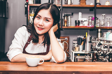 Portrait of woman barista small business owner smiling behind the counter bar with cup of coffee in a cafe