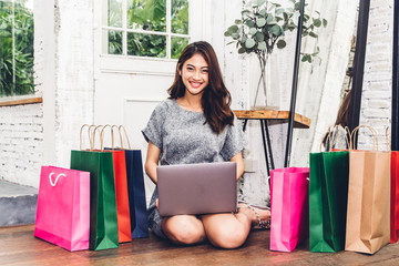 Beautiful woman shoping online with technology of laptop computer and colorful shopping bag sitting on the floor at home