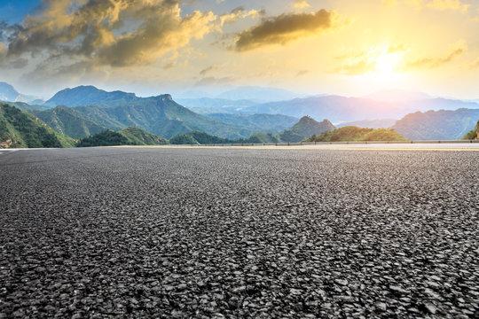 Empty asphalt road and mountain natural landscape at sunrise
