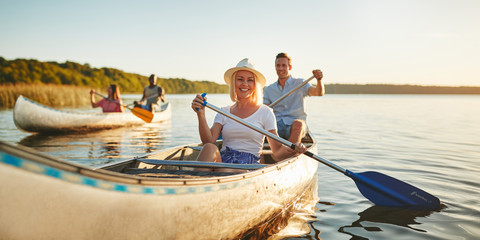 Smiling woman canoeing with friends on a lake in summer