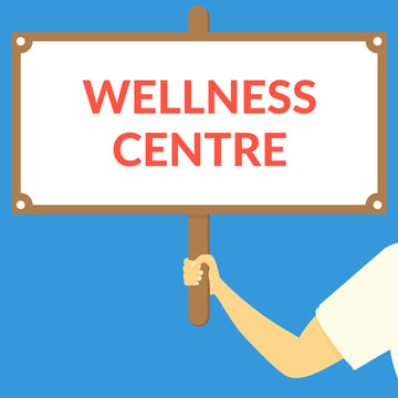 WELLNESS CENTRE. Hand holding wooden sign