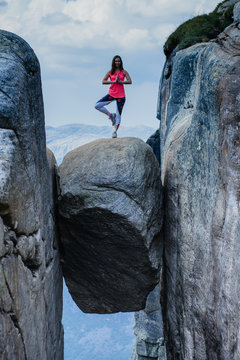 Young yoga woman balancing on stone, Kjerag, Norway. Mountains extreme vacations adventure tourist crazy travel concept. Vertical shot.
