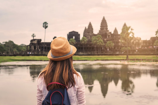 Young woman traveler looking at Angkor Wat, Khmer architecture heritage in Siem Reap, Cambodia