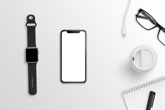 Smart mobile phone and watch on clean office desk. Black and white composition. Flat lay.