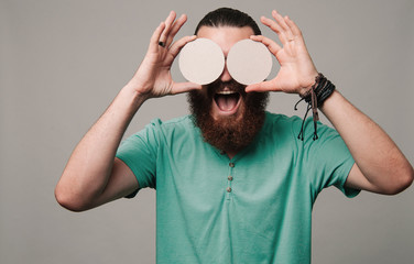 Young bearded hipster covering eyes with two blank circles.