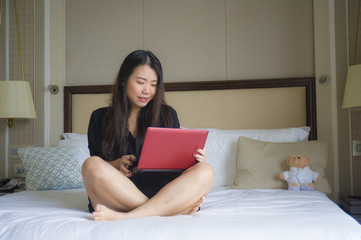 lifestyle portrait of young happy and relaxed Asian Korean woman at hotel room bed working with laptop computer cheerful in business travel