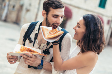 Happy couple of tourist eating pizza on street