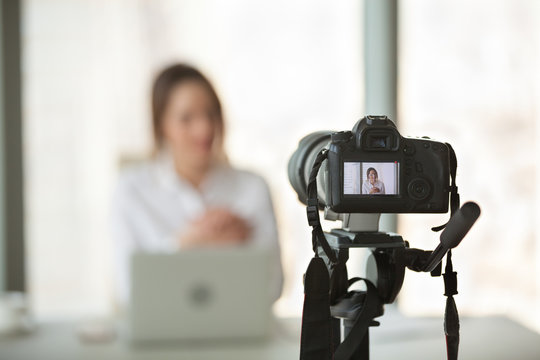 Professional video camera recording successful businesswoman giving online training or filming business course, digital device shooting vlog or interview of company boss or streaming live presentation