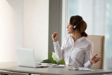 Excited playful businesswoman wearing headset listen to favorite music during office break, female worker dancing and singing in imaginary microphone, woman relax enjoying tracks playing at laptop app