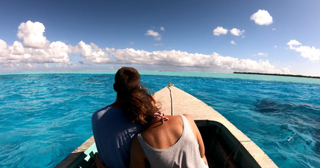 a couple in a boat on a lagoon in French