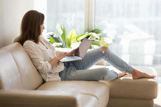 Calm female working at laptop sitting on cozy sofa, happy girl browsing internet or shopping online during sunny weekend at home, woman spending day off at home, relaxing on couch with computer