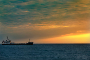 Fishing boat in the open sea on the horizon during sunset