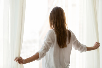Back view of millennial woman open white curtains in modern light apartment, happy female look out of window enjoying beautiful city view, admiring skyscrapers or watching people during sunny morning
