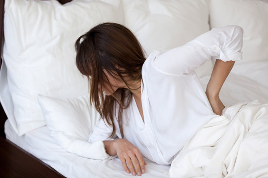 Tired young woman waking up in white bedroom feeling back pain, exhausted female suffering from sudden discomfort after bad sleep in incorrect posture, girl having backache not relaxed at night