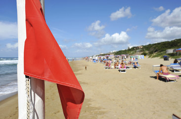A red warning flag on the beautiful beaches of the tyrrenian sea.  Sabaudia, Lazio, Italy