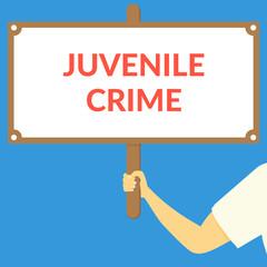 JUVENILE CRIME. Hand holding wooden sign