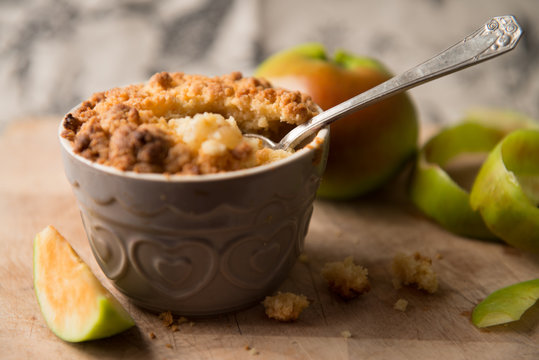 Apple Crumble Dessert with Apple Peal on Rustic Wooden Surface