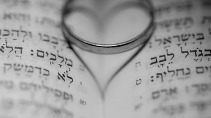 Close up of the Hebrew Jewish bible with a weeding ring creating a heart shape shadow