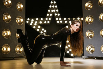 hot kinky woman wearing latex rubber catsuit and fetish corset posing in the black studio with yellow lighting bulbs