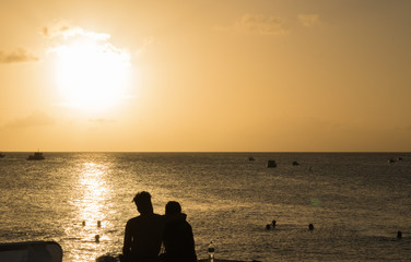 A young couple in love sits in an embrace and looks at the sunset over the horizon of the sea, swimming people and fishing boats in the distance. Silhouettes. Concept: Holiday together.