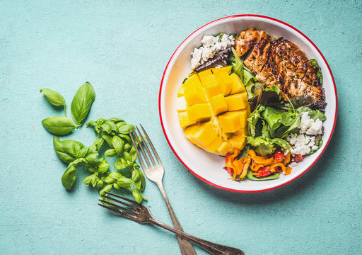 Tasty summer salad with roasted chicken breast and mango in bowl with cutlery on light blue background, top view. Healthy low carb lunch
